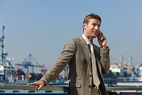 portrait of businessman talking on mobile phone in front of harbour scenery