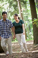 Hispanic couple holding hands in woods