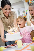 Hispanic mother giving cake to daughter at birthday party