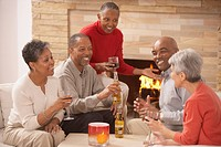 Group of middle_aged friends drinking by fireplace