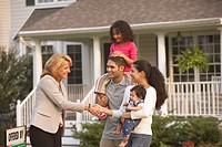 Hispanic family shaking hands with real estate agent
