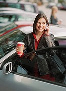 Woman getting into car holding coffee and cell phone