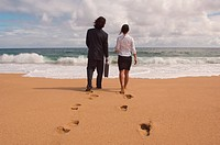 Businessman and businesswoman walking towards ocean