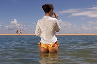 Pacific Islander woman talking on cell phone in ocean