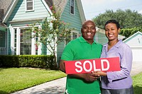 African couple holding Sold sign in front of house