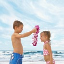 Boy giving flower lei to girl at beach