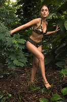 Hispanic woman wearing camouflage bikini in jungle (thumbnail)