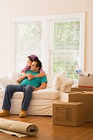 Hispanic couple on sofa in new home