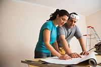 Hispanic couple remodeling interior of home
