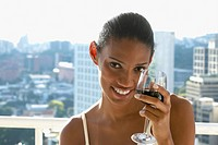 African woman drinking wine on balcony