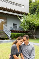 Hispanic couple hugging in front of house