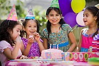 Hispanic girls at outdoor birthday party