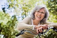 Senior Hispanic woman leaning on bicycle outdoors