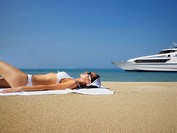 Pacific Islander woman sunbathing on beach (thumbnail)