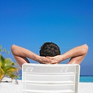 Rear view of man sitting in beach chair