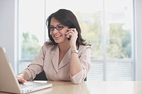 Hispanic businesswoman typing on laptop and talking on cell phone