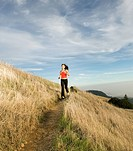 Asian woman jogging on hillside
