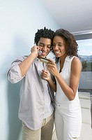 African couple using credit card on cell phone