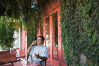 Hispanic man talking on cell phone at restaurant