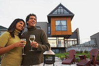 Couple holding wine in front of house