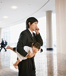 Asian father carrying baby daughter
