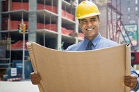 Hispanic businessman holding blueprints