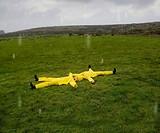 Hispanic couple in rain gear laying in grass
