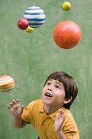 Hispanic boy looking at solar system model