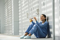 Hispanic nurse eating fruit on floor