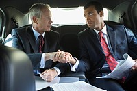 Businessmen shaking hands in limousine