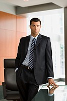 Hispanic businessman leaning on table