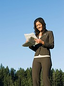 Mixed race businesswoman reading newspaper outdoors