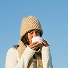 Mixed race woman drinking coffee outdoors