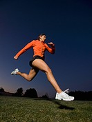 Mixed race woman running on grass