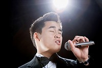 Asian man in tuxedo singing into microphone with eyes closed