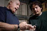 Refrigeration technicians examining wires