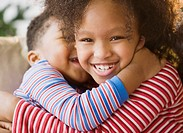 Close up of African American brother and sister hugging