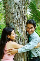 Hispanic couple hugging tree