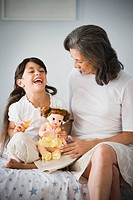 Hispanic grandmother and granddaughter with doll in bedroom