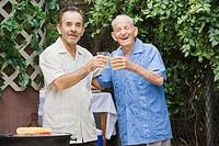 Hispanic men toasting on patio