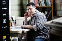 Hispanic man using laptop in workshop