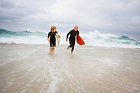Father and son running out of ocean with surfboards