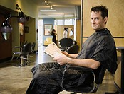 Man reading in hair salon chair