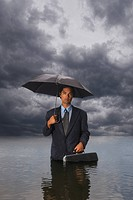 Hispanic businessman standing in water