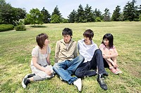 Young men and young women sitting on the grass in the park