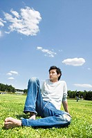 Young man sitting on the grass (thumbnail)