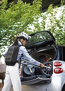 Mid_Adult Woman Putting Bicycle into Car Trunk