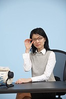 Businesswoman with Eyeglasses Sitting at Desk
