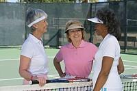 Three women talking at tennis court