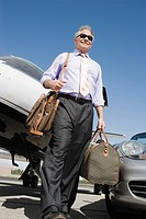 Senior businessman in front of car and airplane low angle view.